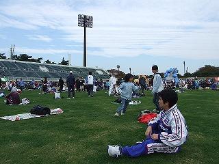 芝生には、準備運動をする人たちや、付き添いで来た子供達も
