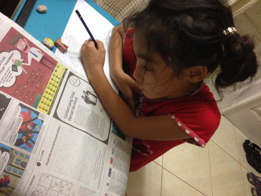 インドネシアの新聞:熱心に文字を追う我が娘